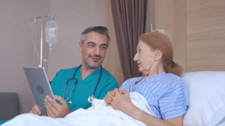 Doctor Talking To senior Patient with tablet In Hospital Bed
