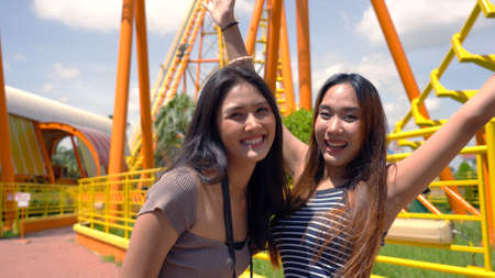Asian friends taking a selfie at the amusement park