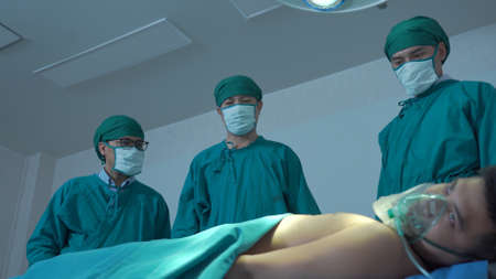 Sad surgeon sitting on floor in corridor at hospital