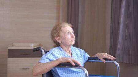Lonely senior woman lying on Wheel Chair at hospital Standard-Bild