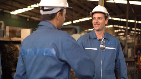 Two engineering in production plant as team discussing in factory