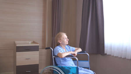 Lonely senior woman lying on Wheelchair at hospital