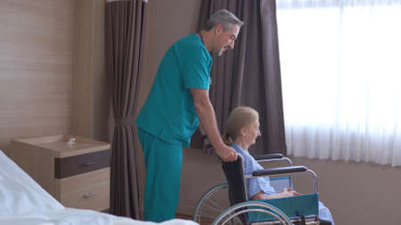 Doctor taking care of mature female patient sitting on wheelchair in hospital