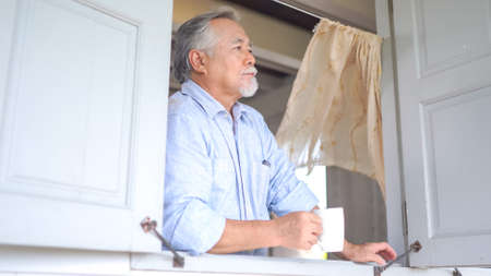 Senior asian man looking by window, holding cup of tea at home Standard-Bild