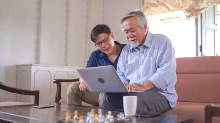 Senior father and his young son using laptop at home