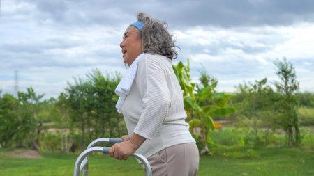 Happy asian senior retired woman using walking frame