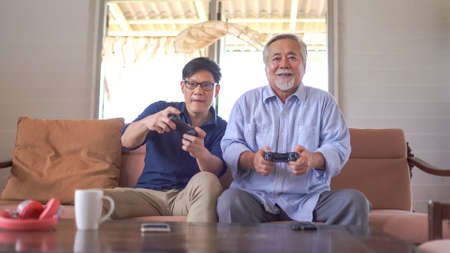 Happy asian father and son enjoy playing video games with joysticks in living room at home Standard-Bild