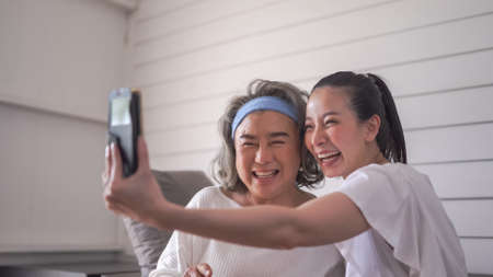 Asian daughter and her senior mother taking selfie photo with mobile phone