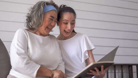 Asian senior woman and daughter reading a book at home Standard-Bild
