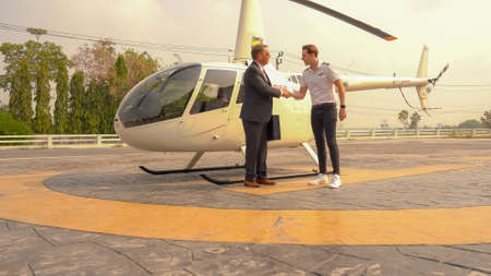 Business man and pilot talking near small private helicopter on a landing point Standard-Bild