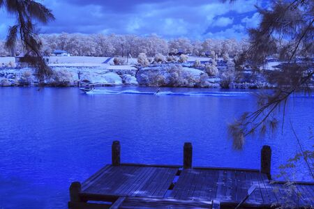 Person water skiing behind a power boat on a river in infra red.