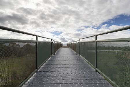A walkway and viewing platform overlooking a lake in a community park.