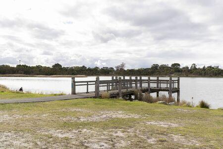 A walk bridge on a large fresh water lake in a community park.