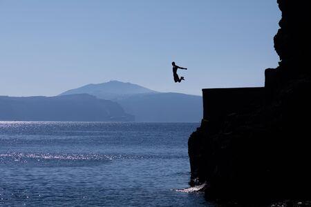 Tourists jumping off a large rock ledge in Amoudi Bay on Santorini Island in Greece.