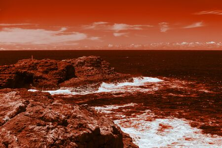 The ocean crashing on rocks with white waves in Kiama New South Wales taken in Infrared Banque d'images