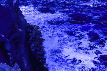 The ocean crashing on rocks with white waves in Kiama New South Wales taken in Infrared