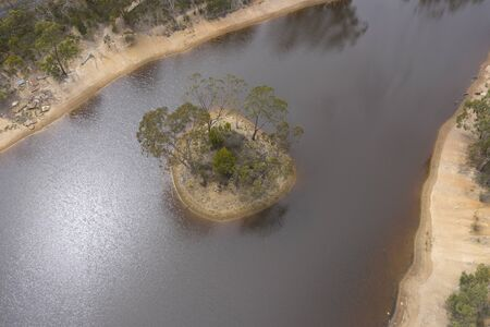 Aerial photograph of mini island in a drought affected water reservoir in rural Australia