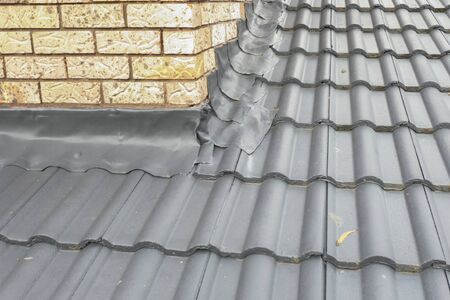 Corner Flashing on a grey tiled roof with cream bricks
