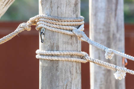 White rope with shackles wrapped around a large wooden pole