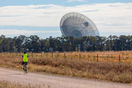 A bicycle rider on a dirt road approaching a large outdoor scientific radio telescope