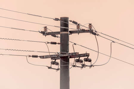 Photograph of a concrete telephone post and cables against an orange sky