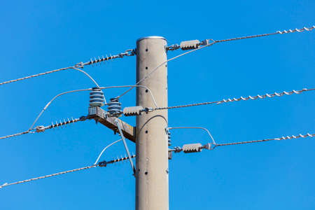 Photograph of a concrete telephone post and cables against a blue sky Banque d'images