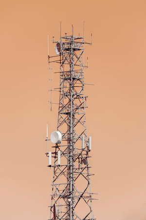 Photograph of a large steel telecommunications tower against an orange sky background