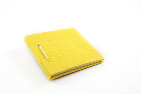 Yellow notebook on white background photo