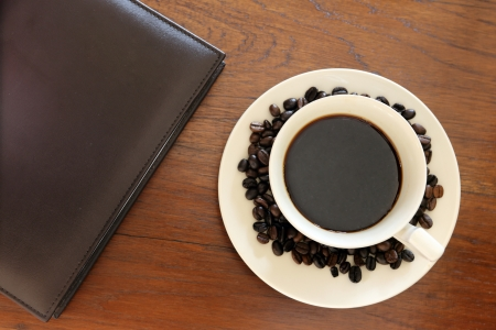 note book with coffee cup on grunge wood photo