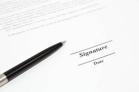 Sign name on document with black pen