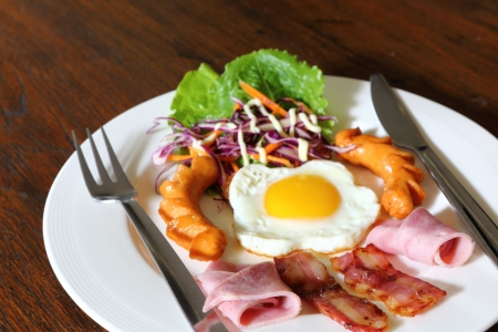 Breakfast with bacon, fried egg,sausages on grunge wood photo