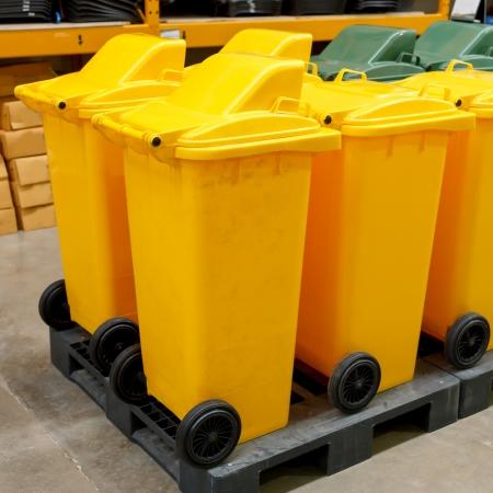 garden waste: Row of large yellow wheelie bins for rubbish