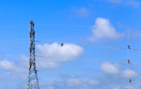 electrician worker at climbing work on high voltage post photo