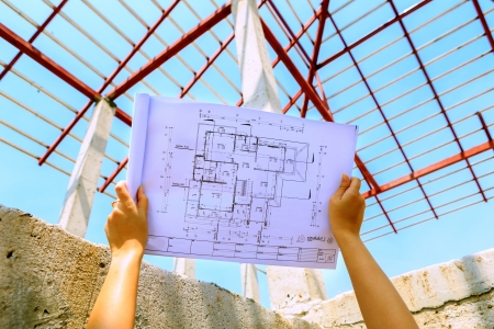 architecture drawings in hand on house building Stock Photo