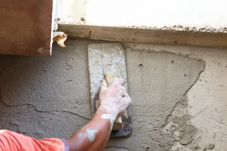 plasterer concrete worker at wall of house construction  photo