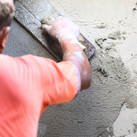 plasterer concrete worker at wall of house construction  版權商用圖片