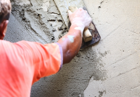 plasterer concrete worker at wall of house construction  Standard-Bild