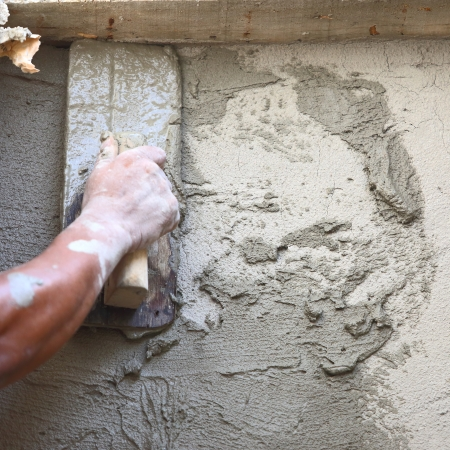 plasterer concrete worker at wall of house construction  Archivio Fotografico