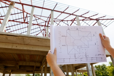 architecture drawings in hand on house building