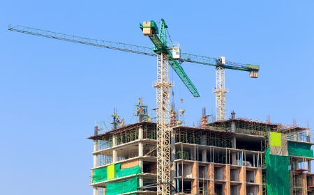 Construction site with crane and workers on blue sky