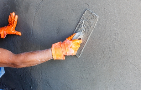 plaster: plasterer concrete worker at wall of house construction  Stock Photo