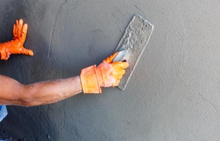 mortero: yesero trabajador concreto en la pared de la construcción de viviendas Foto de archivo