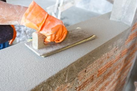 plasterer: plasterer concrete worker at wall of house construction  Stock Photo