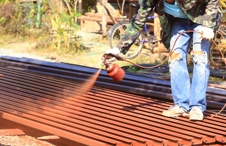 worker spray red color on roof steel for house construction