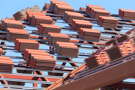 roof under construction with stacks of roof tiles for home building photo
