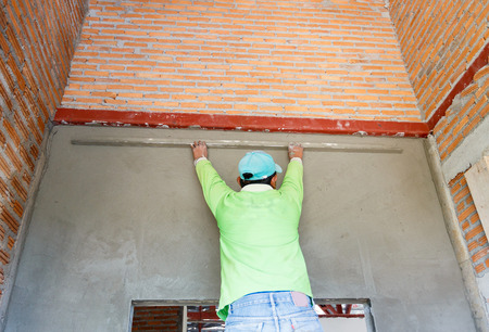plasterer concrete worker at wall of house construction  Stock fotó