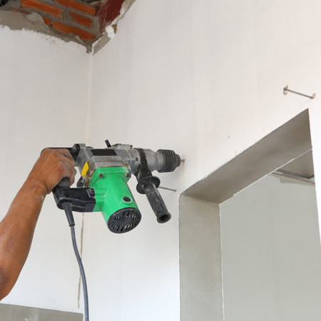 worker use driller for drill wall photo