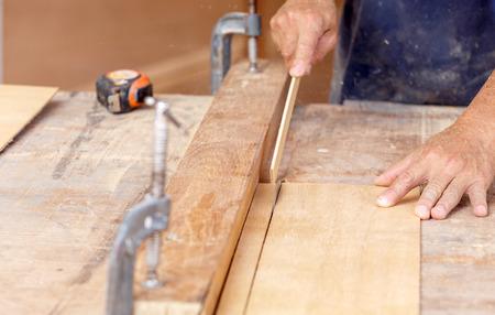 carpenter use saw cut wood for make new furniture photo