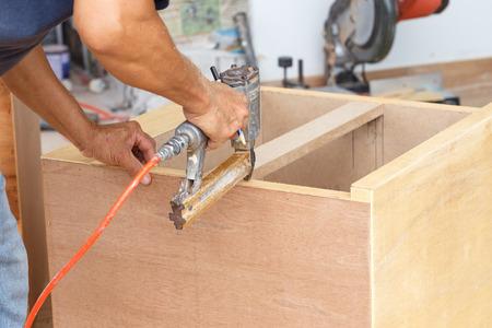 airgun: carpenter used air-gun for make new furniture  Stock Photo