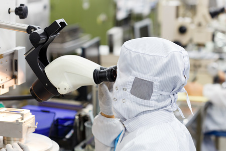 Operator in factory use microscope Stock Photo